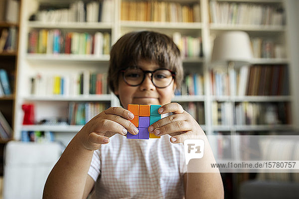 Smiling little boy holding cube made of building blocks