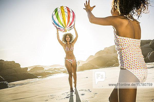 Glückliche Mutter spielt mit Tochter mit aufblasbarem Ball am Strand