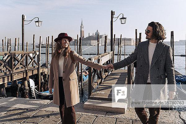 Junges Paar geht Hand in Hand an der Uferpromenade von Venedig  Italien