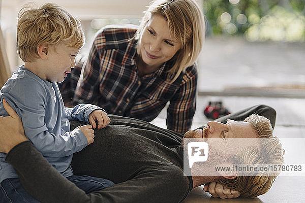 Glückliche  entspannte Familie  die zu Hause gemeinsam auf dem Boden liegt