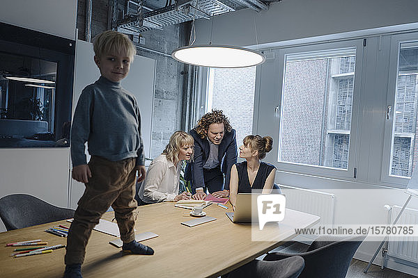 Boy standing on table in office with business team having a meeting