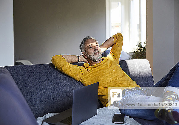 Mature man relaxing on couch at home