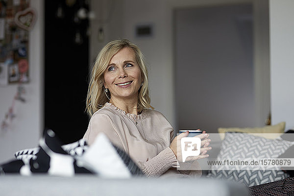 Smiling blond woman relaxing at home sitting on couch