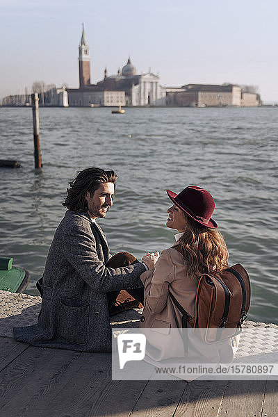 Junges Paar sitzt am Wasser in Venedig  Italien