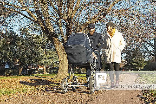 Paar zu Fuß mit Kinderwagen im Park