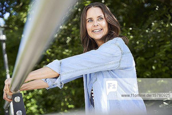 Porträt einer glücklichen brünetten Frau  die sich im Freien an ein Geländer lehnt