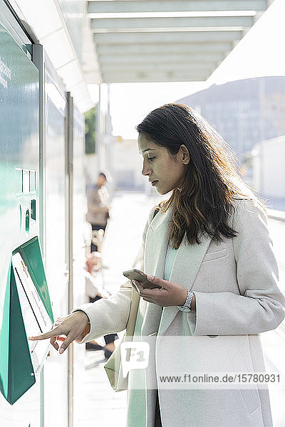 Junge Frau benutzt Fahrkartenautomat an Straßenbahnhaltestelle
