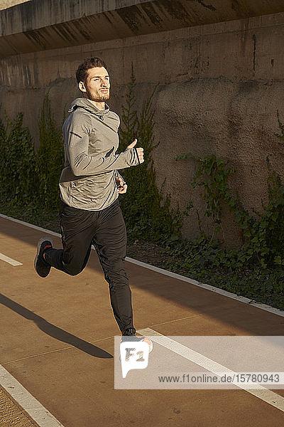 Mann läuft auf einer Straße im Sonnenlicht