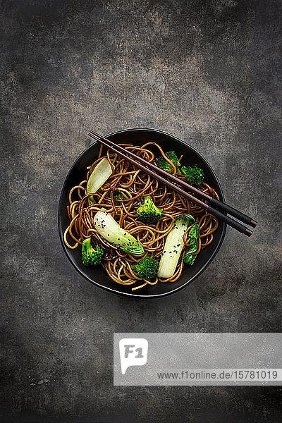Draufsicht auf eine Schüssel Soba-Nudeln mit Pak Choi und Brokkoli  Sojasauce und schwarzem Sesam