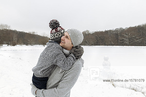 Happy father carrying this son in winter landscape