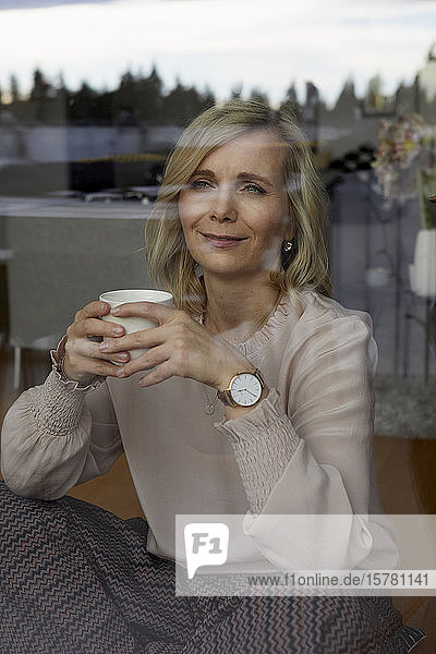 Smiling blond woman holding coffee cup behind windowpane at home