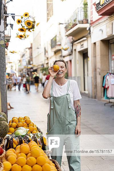 Porträt einer lachenden jungen Frau auf der Einkaufsstraße  die ihr Auge mit einer Orange bedeckt