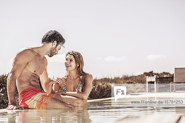 Young couple having fun together at a swimming pool