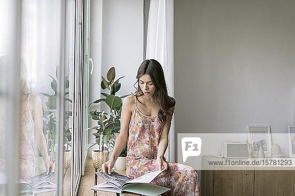 Junge Frau sitzt zu Hause am Fenster mit einem Album