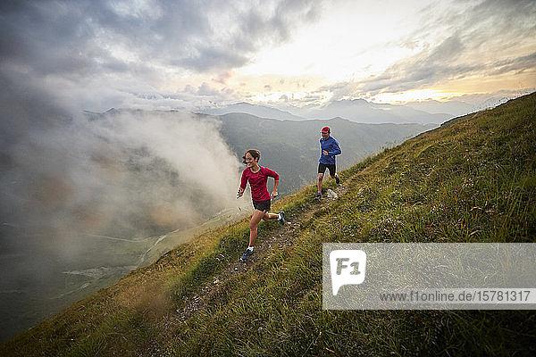 Mann und Frau laufen in den Bergen