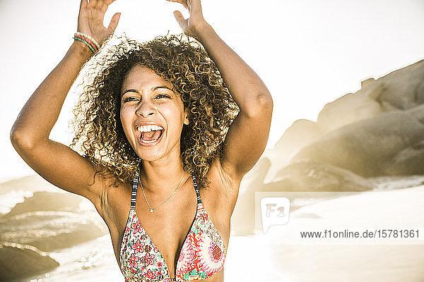 Unbeschwerte junge Frau amüsiert sich am Strand