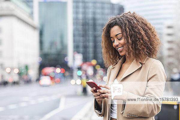 Lächelnde junge Frau benutzt Handy in der Stadt  London  UK