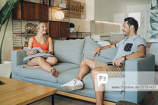Glückliches Paar sitzt auf der Couch im Wohnzimmer