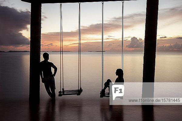 Couple on a swing at the sea at sunset  Maguhdhuvaa Island  Gaafu Dhaalu Atoll  Maldives
