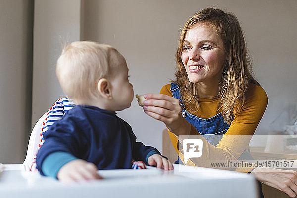 Frau  die ihren kleinen Sohn zu Hause füttert