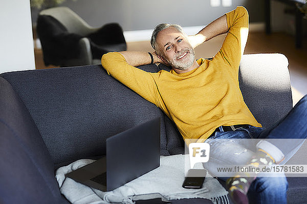 Portrait of smiling mature man relaxing at home