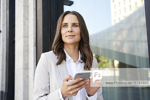 Portrait of confident businesswoman with cell phone in the city