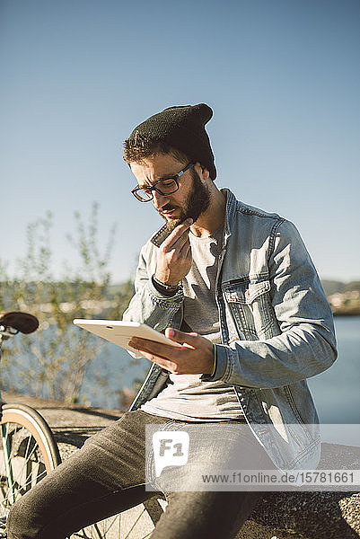 Young man sitting on wal by the sea  using digital tablet