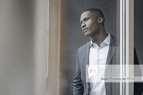 Porträt eines jungen Geschäftsmannes  der aus dem Fenster schaut