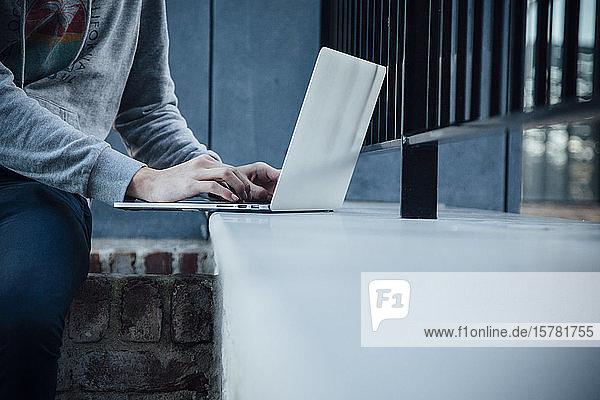 Teenager mit Laptop in der Stadt
