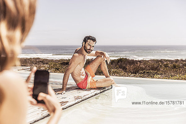 Woman taking smartphone picture of young man at the poolside