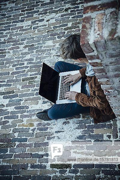 Teenager  der einen Laptop benutzt und auf einem Steinboden in der Stadt sitzt