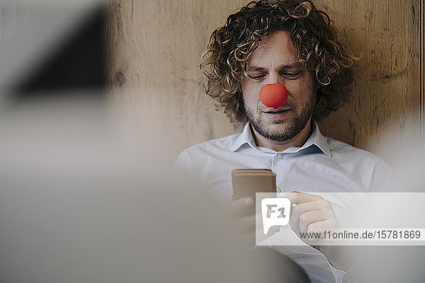 Businessman with red clown nose using cell phone in office