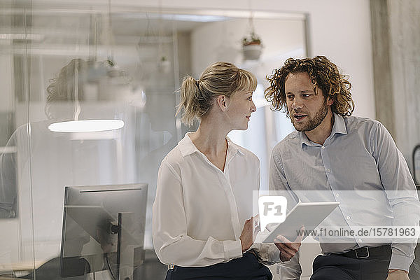 Businessman and businesswoman with tablet talking in offce