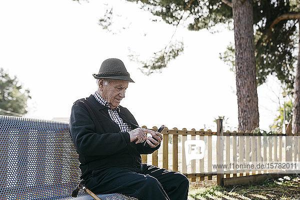 Alter Mann mit  auf Bank sitzend  mit Smartphone