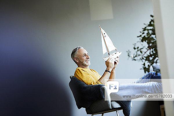 Smiling mature man at home holding model sailboat