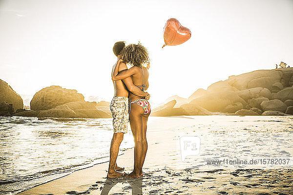 Paar mit herzförmigem Ballon  das sich bei Sonnenuntergang am Strand umarmt