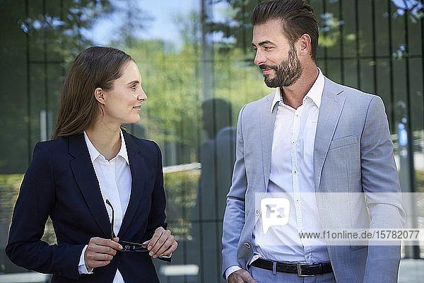 Geschäftsmann und Geschäftsfrau mit Handy in der Stadt