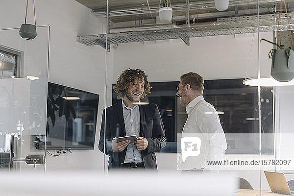 Two happy businessmen talking in office