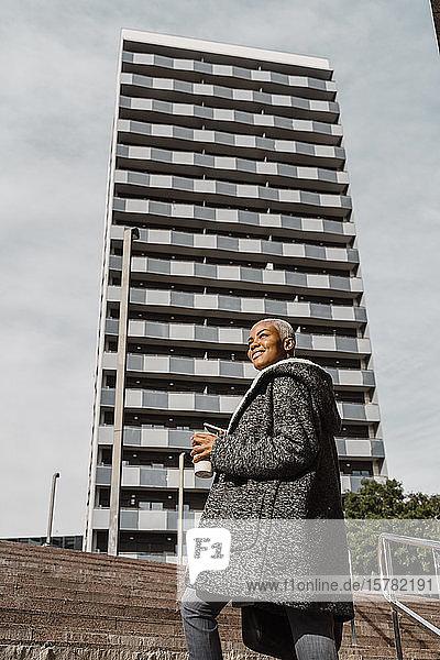Stilvolle Geschäftsfrau  die mit Smartphone und Kaffeetasse durch die Stadt pendelt