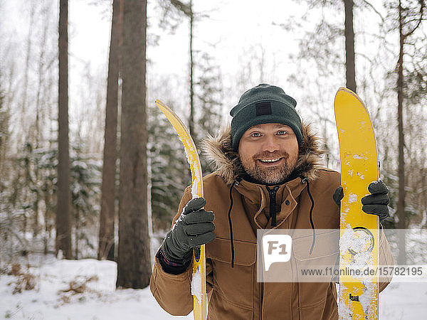 Portrait of happy man with skis