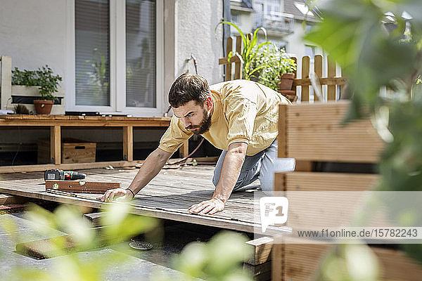 Junger Handwerker baut Holzterrasse vor seinem Haus