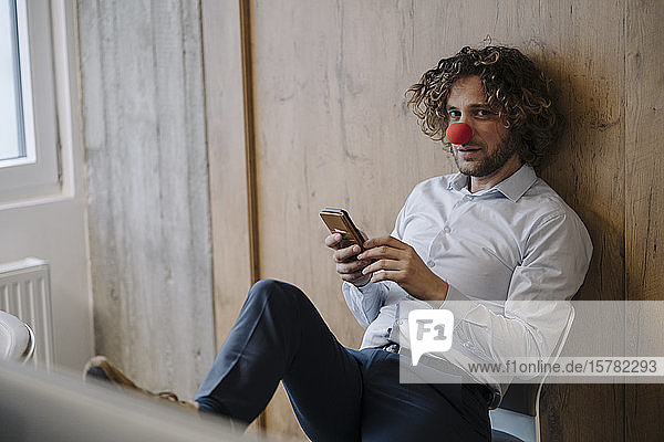 Portrait of businessman with red clown nose using cell phone in office