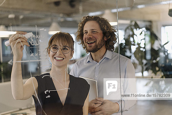 Happy businessman and businesswoman working on a project in office