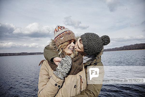 Junger Mann küsst seine Freundin vor einem See