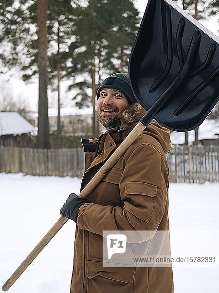 Portrait of smiling man with snow shovel