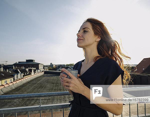 Lächelnde rothaarige Frau bei einer Kaffeepause auf der Dachterrasse