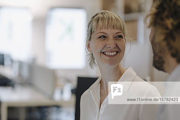 Portrait of smiling businesswoman looking at businessman in offce
