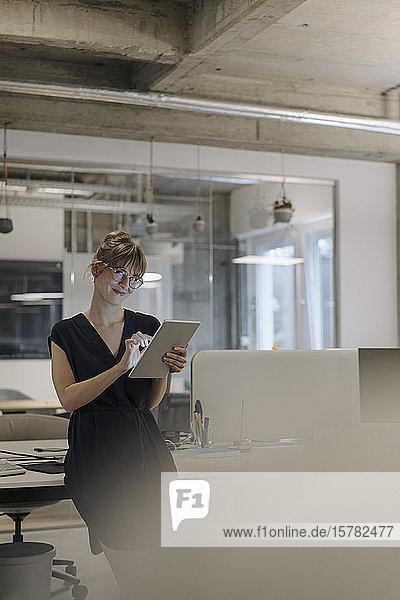 Zuversichtliche Geschäftsfrau benutzt Tablet im Büro