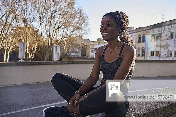 Junge lächelnde Sportlerin sitzt an einer Wand