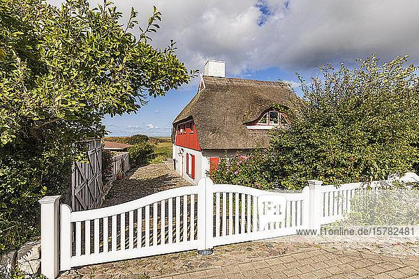 Deutschland  Mecklenburg-Vorpommern  Ahrenshoop  Weißes hölzernes Eingangstor eines rustikalen Hauses mit Strohdach